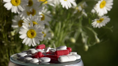 Pills against a green background with flowers Stock Footage