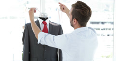 Handsome tailor measuring suit on mannequin Stock Footage