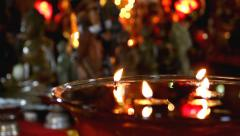 Candles float in waterbowl in Buddhist temple Stock Footage