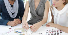 Design team looking at costume jewelry and speaking together - stock footage