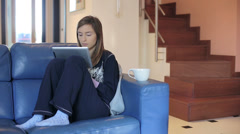 Tablet Young woman websurfing on internet while drinking coffee - stock footage
