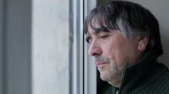 sad and pensive mature man at the window - stock footage