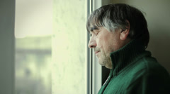 worried and pensive mature man looking at the window - stock footage