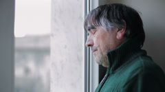portrait of depressed mature man looking at the window - stock footage