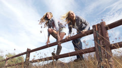 Beautiful young women jumping across fence running - stock footage