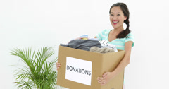 Pretty brunette holding donation box full of clothes Stock Footage