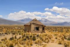 typical bolivian house with volcanoes - stock photo