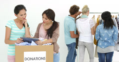 Team of smiling workers using tablet beside donation box - stock footage