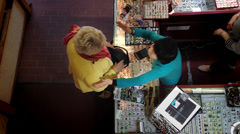 Overhead shot of vendor and customer in store. Stock Footage