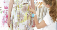 Stock Video Footage of Pretty fashion designer measuring floral dress on a model