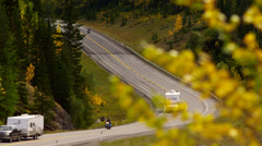 Kananaskis trail cars motorcycles round curve in fall - stock footage