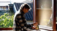 Man painting wooden window frame with clear varnish Stock Footage