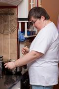 mentally disabled woman is cooking - stock photo