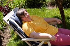Disabled woman basks in a deck chair Stock Photos