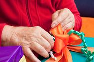 Stock Photo of senior citizen wrap or unpack gifts, closeup
