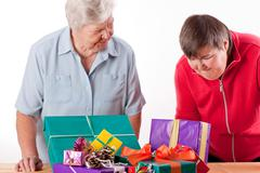 senior with mentally handicapped woman consider gifts - stock photo