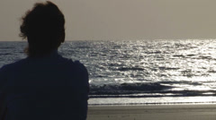 Lonely man near the ocean looking into the distance, slow waves - stock footage