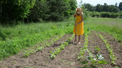 Barefoot gardener lady in dress and hat grub weed in farm Stock Footage