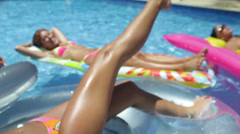 Sexy hot girl  wearing a bikini on an air matress in a pool Stock Footage