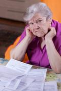 Elderly woman sits in front of papers and desperate Stock Photos