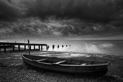 old decayed rowing boats on shore of lake with stormy sky overhead - stock photo