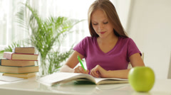 Cheerful girl sitting at table writing in notebook grabbing apple  Stock Footage