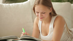 Cheerful girl lying on couch writing in workbook looking at camera and smiling Stock Footage
