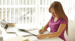 Cheerful girl sitting at table with books and laptop writing in workbook looking Stock Footage