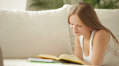 Charming girl lying on couch studying reading book looking at camera  Stock Footage