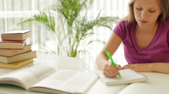 Bored schoolgirl sitting at table writing in notebook and putting her head  Stock Footage