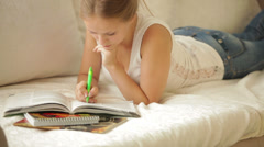Blonde girl lying on couch writing in workbook looking at camera and smiling. Stock Footage