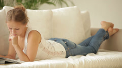 Pretty girl lying on couch writing in workbook looking at camera and smiling. Stock Footage