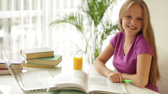 Cute girl sitting at table writing in workbook looking at camera and smiling. Stock Footage
