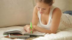 Cute girl lying on couch writing in workbook looking at camera and smiling Stock Footage
