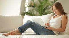 Söpö blondi tyttö rentoutua sohvalla olohuoneessa ja käyttää kannettavaa tietoko Arkistovideo