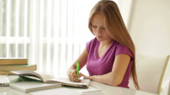 Pretty girl sitting at table writing in workbook loking at camera and smiling Stock Footage