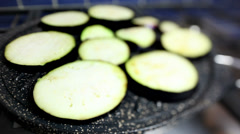Slices of eggplants grilled on non-stick pan on ring. Stock Footage