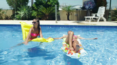 Two hot girls having fun in a pool  Stock Footage