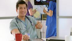 Medical intern in hospital lounge using tablet pc smiles Stock Footage