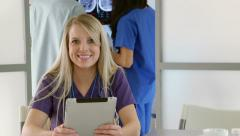 nurse in clinic using tablet pc looks and smiles - stock footage