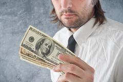businessman holding united states dollars - stock photo