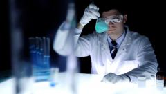 Scientist in Laboratory Holding a beaker Shaking Stock Footage
