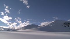 Rolling mountains in sunlight and blue sky, Antarctica Stock Footage
