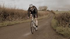 Male road bike racer rider in lycra shorts and winter windproof jacket, helmet Stock Photos
