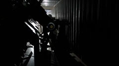 Silhouettes of industrial workers loading heavy piece of machinery in contain Stock Footage
