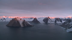 Sunset glows on mountain tops. Aerial, Antarctica Stock Footage