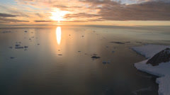 Sunset lights up Antarctic sea & bergs. Aerial Stock Footage