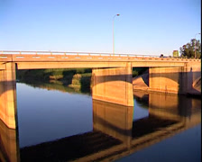 A bridge over a river, man cycles over it. Stock Footage