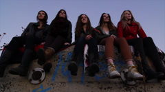 Five Teen Girls Sit On A Wall, Look Into The Distance, One Points Stock Footage