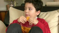 Boy eating chips Stock Footage